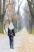 Mujer vestida con ropa negra y botas en callejón otoñal — Foto de Stock