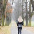 Woman wearing black clothes and boots in autumnal alley — Stock Photo #31085947