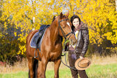 Equestrian with her horse in autumnal nature — Stock Photo