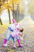 Mother with her daughter in autumnal alley — Stock Photo