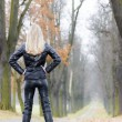 Woman wearing black clothes and boots in autumnal alley — Stock Photo #31765507