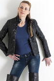 Portrait of standing woman wearing jeans and black jacket — Stock Photo