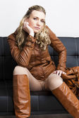 женщина, одетая коричневый куртку и сапоги, сидя на диване — Стоковое фото