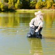 Stock Photo: Womfishing in pond