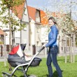 Woman with a pram on spring walk — Stock Photo #32073837