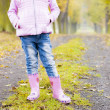 Detail of little girl wearing rubber boots in autumnal alley — Stock Photo
