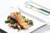 Salmon fillet with warm spinach and bacon salad — Stock Photo