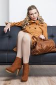 Woman wearing brown coat with a handbag sitting on sofa — Stock Photo