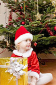 Little girl as Santa Claus with Christmas present — Stock Photo