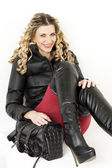 Portrait of sitting woman wearing fashionable clothes and boots — Stock Photo