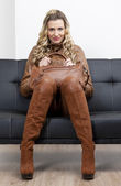 Woman wearing brown clothes and boots with a handbag sitting on — Stockfoto