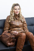 Woman wearing brown clothes and boots with a handbag sitting on — Stock Photo