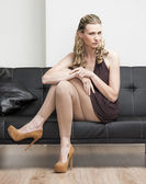 Woman wearing brown pumps sitting on sofa — Stock Photo