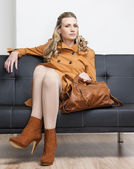 Woman wearing brown coat with a handbag sitting on sofa — Стоковое фото