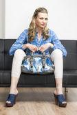 Woman wearing denim clogs with a handbag sitting on sofa — Stock Photo