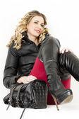 ファッショナブルな服とブーツを着て座っている女性の肖像画 — ストック写真