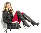 Sitting woman wearing fashionable clothes and boots with a handb — Stock Photo