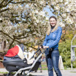Woman with a pram on spring walk — Stock Photo #38334081