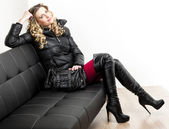 Woman wearing fashionable clothes sitting with a handbag on a so — ストック写真