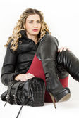 Portrait of sitting woman wearing fashionable clothes and boots — ストック写真