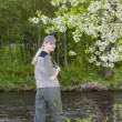 Stock Photo: Womfishing by river in spring
