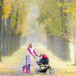 Mother and her daughter in autumn alley — Stock Photo