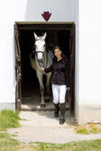 Equestrian with horse in stable — Stock Photo