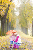 Mother and her daughter with umbrella in autumnal alley — Stock Photo