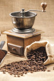 Still life of coffee beans in jute bag with coffee grinder — Stock Photo