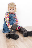 Little girl putting on boots — Stock Photo