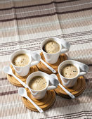 Cups of coffee on place mats — Stock Photo