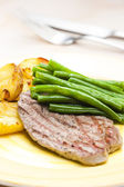 Beefsteak with green beans and garlic potatoes — Stock Photo