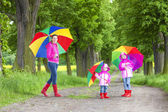 Mother and her daughters with umbrellas in spring alley — Stock Photo