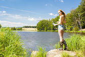 Young woman fishing at pond in summer — Stock Photo