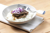 Beef rump steak with onion and rice — Stock Photo