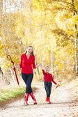 Mother with her daughter with umbrellas in autumnal alley — Foto de Stock