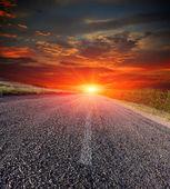 Асфальтовая дорога на фоне заката — Стоковое фото