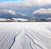 Snowy meadow under mountains — Stock Photo