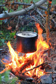 Kettle on tourist camp fire — Stock Photo
