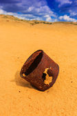 Broken rusty can on sand — Stok fotoğraf