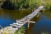 Wooden bridge on river — Stock Photo