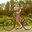 Young woman in dress posing with retro bicycle in the park. — Foto de Stock