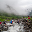 Hikers group cross the mountain river — Stock Photo #32286475