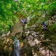 Stock Photo: Hikers climb rocks near waterfall