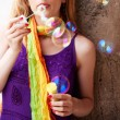 Woman blowing colorful soap bubbles — Stock Photo #5331026