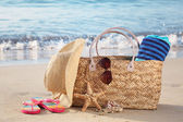 Summer beach bag on sandy beach — Stock Photo