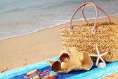 Summer beach bag on sandy beach — Stock Photo
