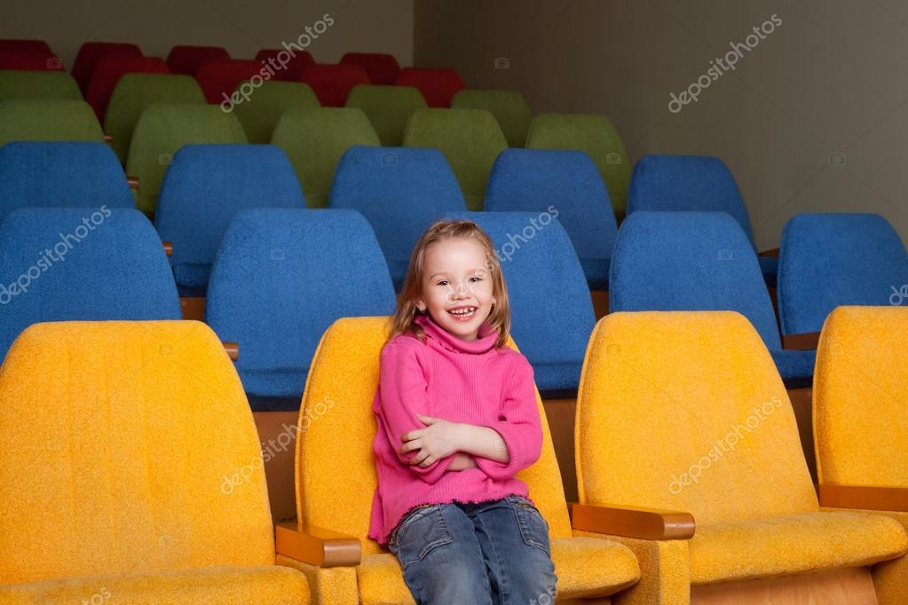 Cute pretty smiling little girl sitting in the cinema hall — Stock Photo #13818476
