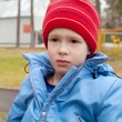 Boy in the cap and coat outdoors - Stock Photo