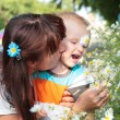 Child smelling the flowers with his mother — Stock Photo